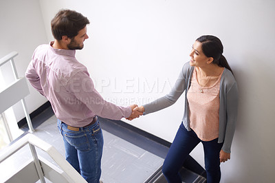 Buy stock photo Shot of a two young people shaking hands in a stairwell