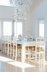 White interior with dining table and chairs and chandelier