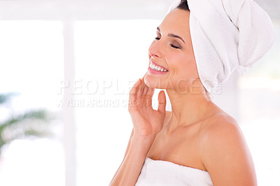 Buy stock photo A woman caressing her skin while standing with her towel wrapped around her body