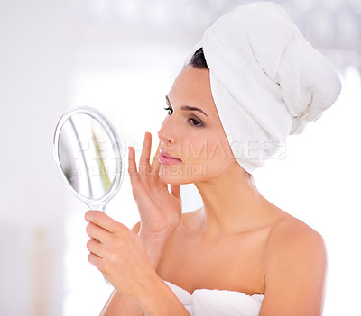Buy stock photo A beautiful woman caressing her skin while holding a hand mirror