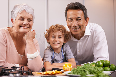 Buy stock photo A young boy cooking in the kitchen with his grandparents
