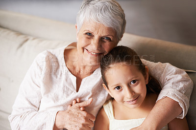 Buy stock photo Portrait of a little girl and her grandma sitting on a sofa