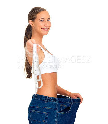 Buy stock photo Portrait of a sporty young woman holding out a tape measure while pulling her pants away from her body