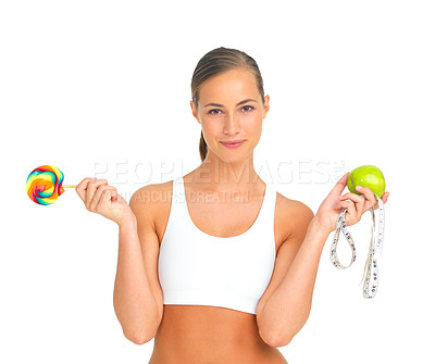 Buy stock photo Portrait of a sporty young woman holding an apple and a lollipop in either hand