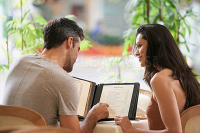 Buy stock photo A happy young couple looking at the menu at a fancy restaurant