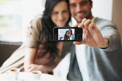 Buy stock photo Cropped shot of an attractive young couple snapping pictures of themselves