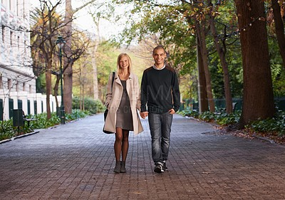 Buy stock photo Full length shot of a young couple walking hand in hand in a park