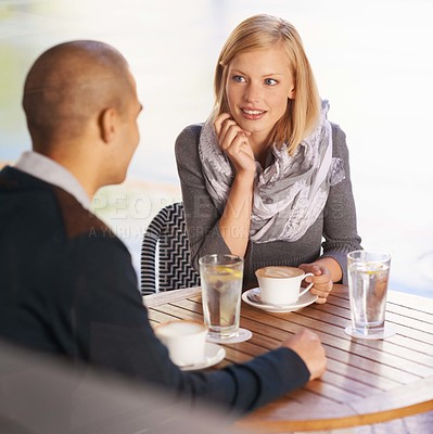 Buy stock photo Shot of a young couple talking and drinking coffee in a cafe