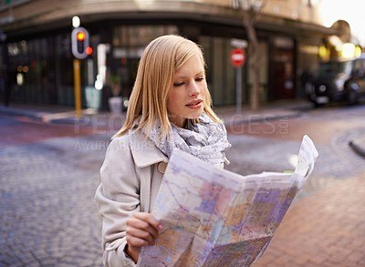 Buy stock photo Shot of a young woman holding a map while touring abroad