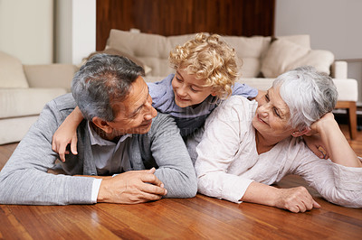 Buy stock photo A little boy lying on top of his grandparents on the floor of their living room