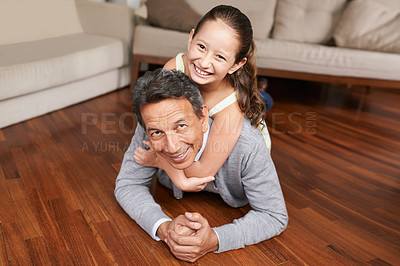 Buy stock photo Shot of a grandfather and granddaughter playing on the floor