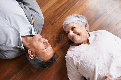 Buy stock photo Shot of a happy-looking elderly couple lying down and smiling