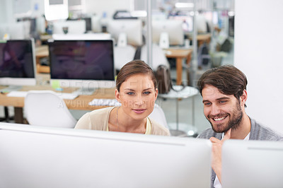 Buy stock photo Shot of a young businessman showing his colleague something on the computer