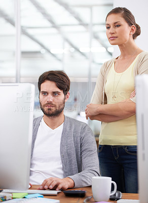 Buy stock photo Shot of a young businesswoman watching her colleague working