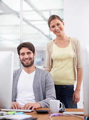 Buy stock photo Shot of two young coworkers smiling at the camera