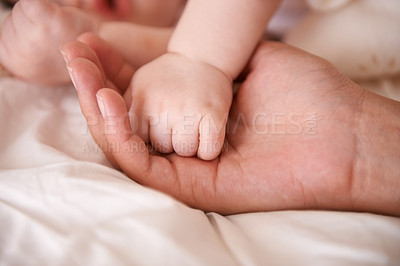 Buy stock photo Cropped shot of a mother holding her baby boy's hand as he sleeps