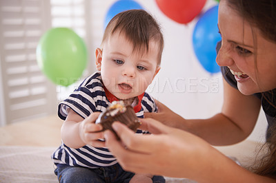 Buy stock photo Cropped shot of a mother giving her baby boy some birthday cake