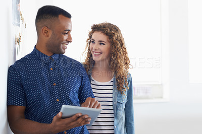 Buy stock photo A young man and woman standing in an office inspecting something on a digital tablet