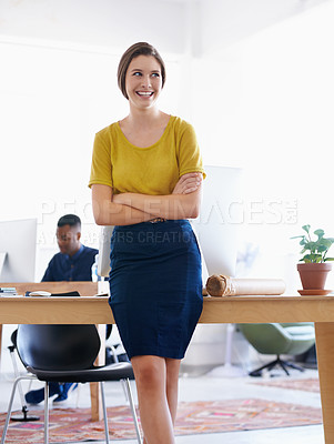 Buy stock photo A young woman in the office with colleagues in the background