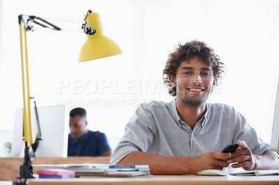 Buy stock photo A handsome young businessman sitting at his desk with his colleague in the background