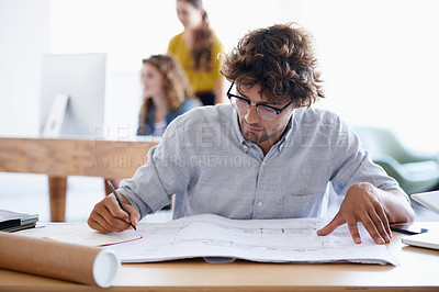 Buy stock photo A young architect sketching building plans