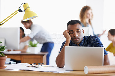 Buy stock photo An ethnic businessman looking bored and tired as he sits behind his desk