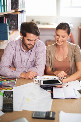 Buy stock photo Shot of young design professionals using a digital tablet while editing images