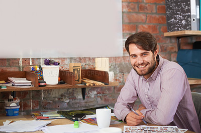 Buy stock photo A handsome young designer smiling as he works in his office