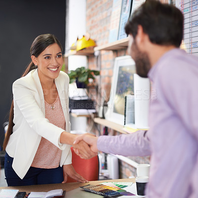 Buy stock photo Shot of two young office professionals shaking hands