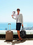 Woman holding a question mark board along with luggage, outdoors