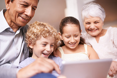Buy stock photo A shot of two kids and their grandparents using a digital tablet while sitting on the sofa