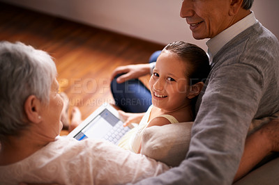 Buy stock photo A little girl using a tablet while sitting with her grandparents