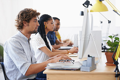 Buy stock photo Shot of a team of designers working on their computers