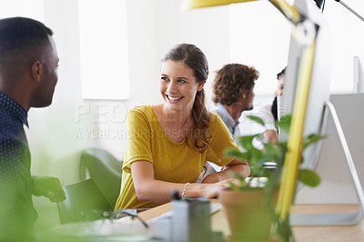 Buy stock photo Shot of a team of designers talking while working on their computers