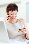 Mature business woman shopping using a credit card and talking on mobile