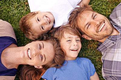 Buy stock photo Portrait of a loving family lying on the grass together