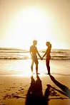 Silhouetted couple holding hands on the beach