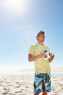 Buy stock photo A handsome teenage boy with a football at the beach