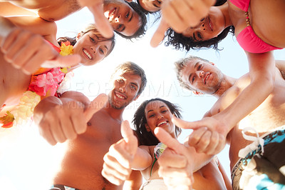 Buy stock photo Happy friends standing in a circle showing thumbs up at the beach