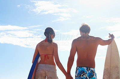Buy stock photo Young couple with surf boards holding hands with blue sky as the background