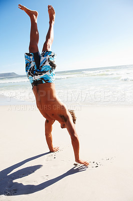 Buy stock photo Portrait of a teenage guy doing handstand at the beach