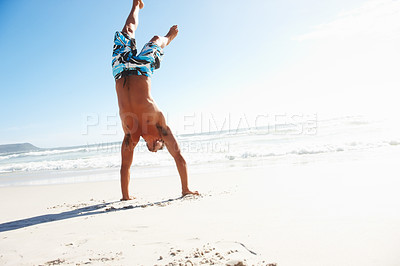 Buy stock photo A young confident man doing handstand at the beach
