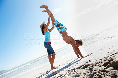 Buy stock photo A boy doing handstand at the beach with the support of a friend