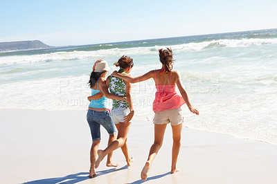 Buy stock photo Rear view of three young teenage girls running on the beach