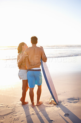 Buy stock photo Rear view of young couple at the beach with a surf board