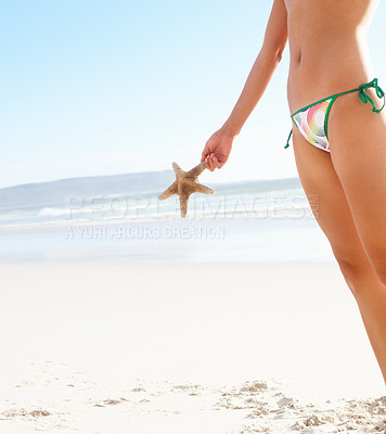 Buy stock photo Mid section image of a young woman at the beach holding a starfish