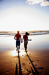 Silhouette image of a young couple running towards the sea