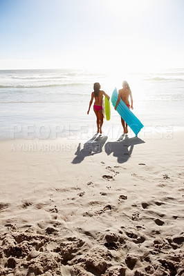 Buy stock photo Rear view of women with floats walking towards the sea
