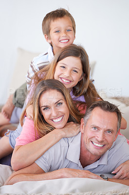 Buy stock photo Portrait of a happy young family of four piled on top of one another