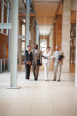 Buy stock photo Group of four business colleagues walking through the hallway